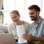 Happy couple working at home on computer on mortgage loan.