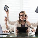 Busy mortgage originator multitasking at desk