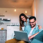 young couple in apartment investigate mortgage loan offerings online